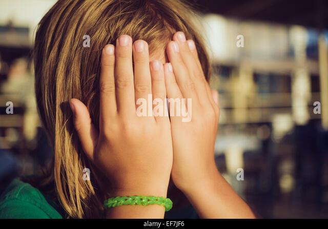 Junge versteckt Gesicht mit Händen Stockbild
