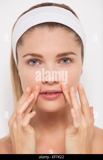 Schöne Frau, die Anwendung der Feuchtigkeitscreme im Gesicht Stockbild