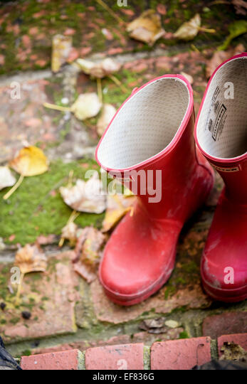 Ein paar rote Hunter Wellington vor einer Haustür Stiefel, umgeben von verlässt. Stockbild