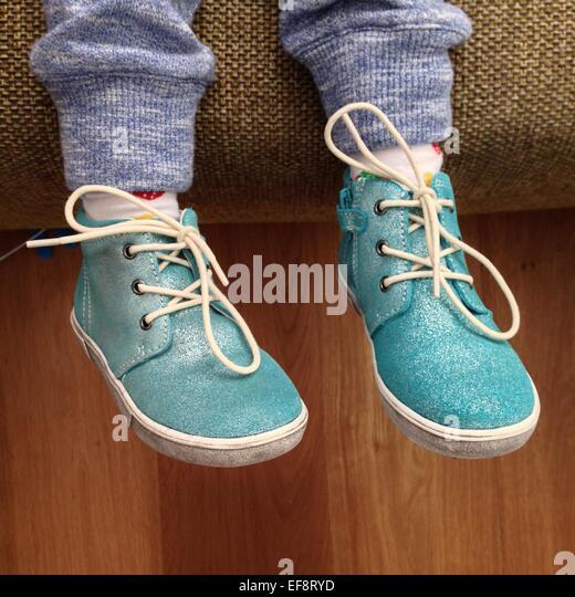 Schuss der Beine des Kindes mit türkisfarbenen Schuhen beschnitten Stockbild