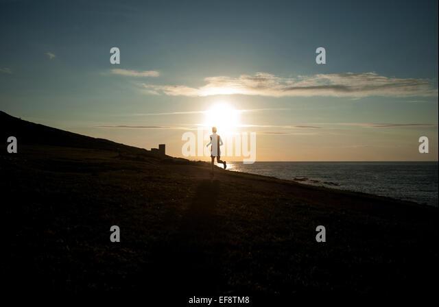 Silhouette der Mann läuft am Strand bei Sonnenuntergang, Galicien, Spanien Stockbild