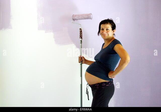 Schwangere Frau Malerei Zimmer Stockbild