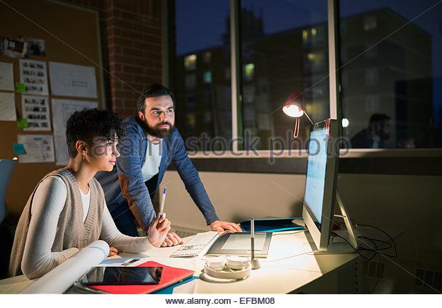 Grafik-Designer arbeiten spät am Computer im Büro Stockbild
