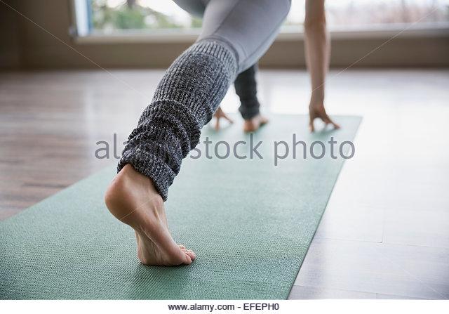 Frau Yoga zu praktizieren im Ausfallschritt posieren auf Matte Stockbild