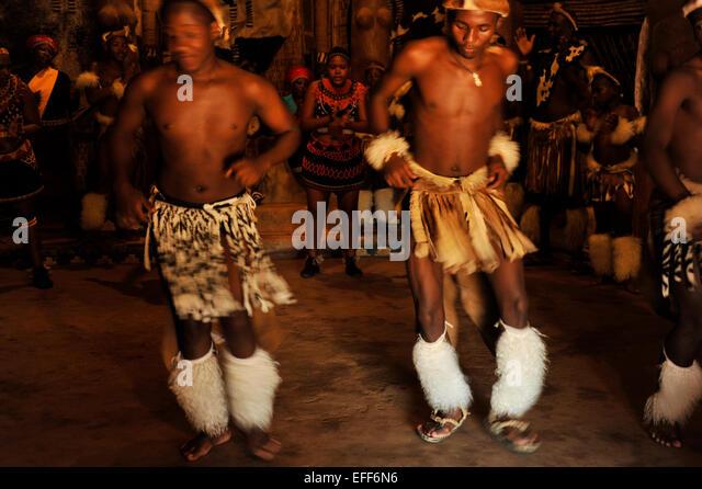 Zwei traditionelle Zulu Tänzer im Zeremoniell Kostüm unterhaltsame Touristen bei Shakaland KwaZulu-Natal Stockbild