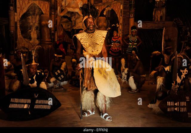 Zulu-Häuptling mit Schild umgeben von Tänzern in Krieger Kleid während des traditionellen Tanzes Stockbild