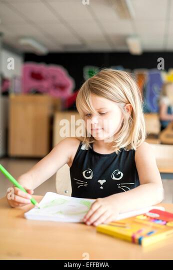 Niedliche Mädchen zeichnen mit Farbstift im Klassenzimmer Stockbild