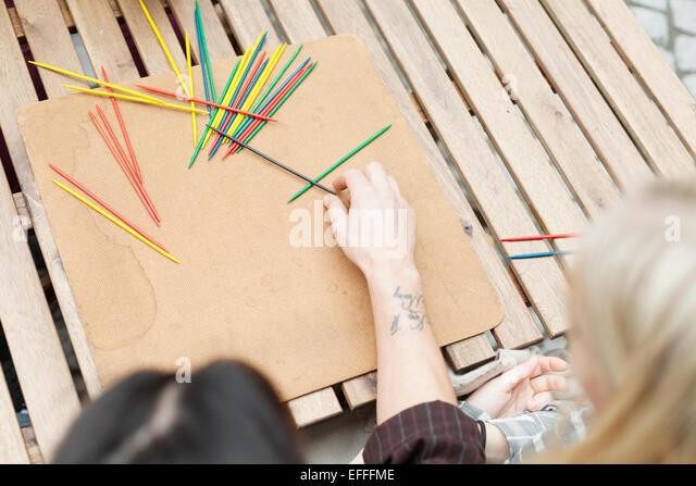 Bild des Paares spielen Mikado an Holztisch beschnitten Stockbild