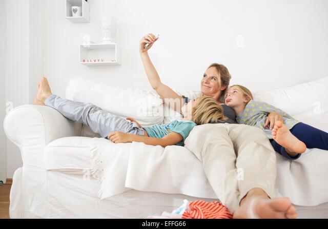 Mutter, Tochter und Sohn auf Couch nehmen ein Selbstporträt Stockbild