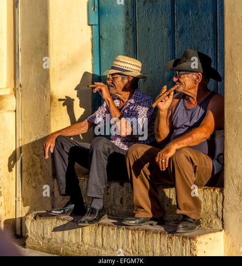 Zwei ältere Kubaner sitzen auf einer Haustür im Abendlicht, rauchen Zigarren, Trinidad, Provinz Sancti Stockbild