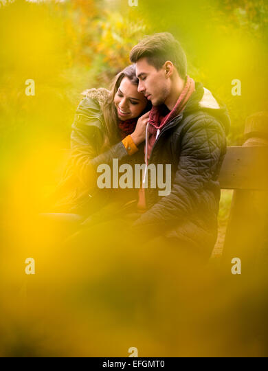 Liebespaar im Herbst Park auf einer Bank sitzend Stockbild