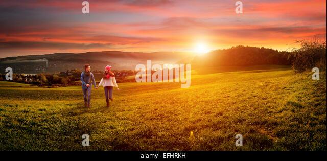 Liebendes Paar Hand in Hand laufen auf dem Feld. schöne Landschaft Stockbild