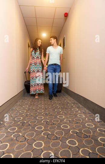Junges Paar am Hotelflur bei der Ankunft stehen auf der Suche nach Raum, mit Koffer. Stockbild