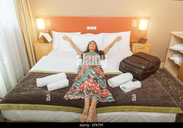 Junge Frau liegt im Bett eines Hotelzimmers Stockbild
