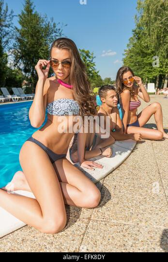 Schöne Frau im Bikini posieren am Rande des Schwimmbades hinter ihren Freunden Stockbild