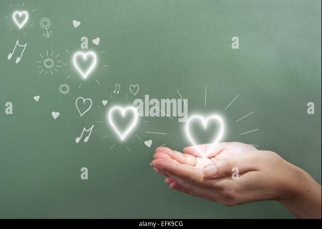 Hände halten einen glühenden Herzen über eine Tafel-Exemplar Stockbild