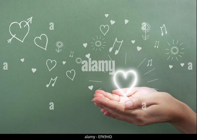 Hände halten einen glühenden Herzen über eine Tafel mit Liebe Symbole Stockbild