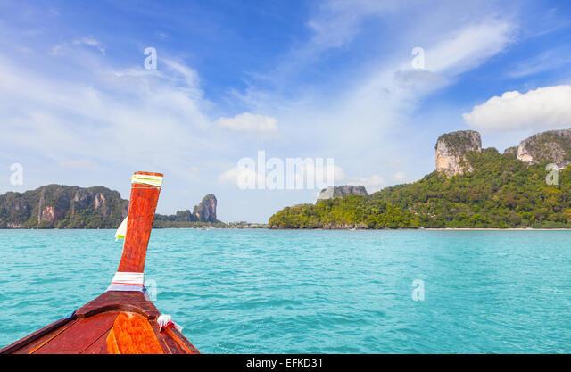 Holzboot und eine tropische Insel im Abstand. Stockbild