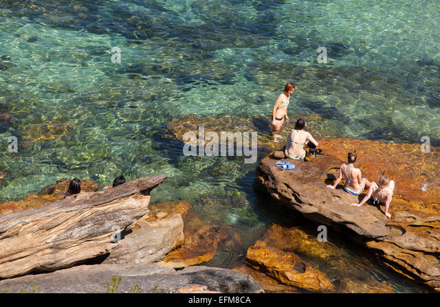 Frauen sitzen auf einem Felsen in Gordons Bay, Sydney, Australien Stockbild