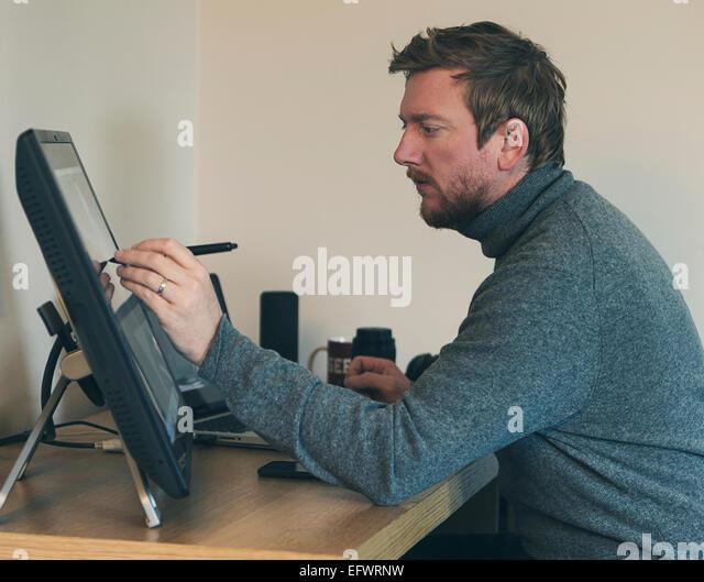 30er Jahre Männlich arbeiten auf Touch-Screen Stockbild