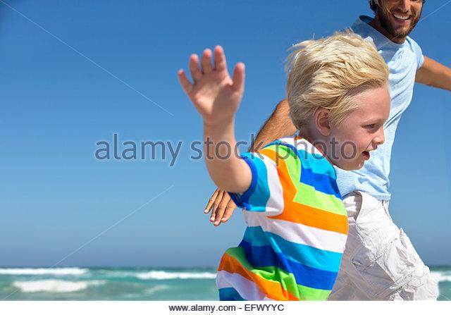Vater und Sohn, lächelnd, mit ausgestreckten, läuft am Sonnenstrand Stockbild
