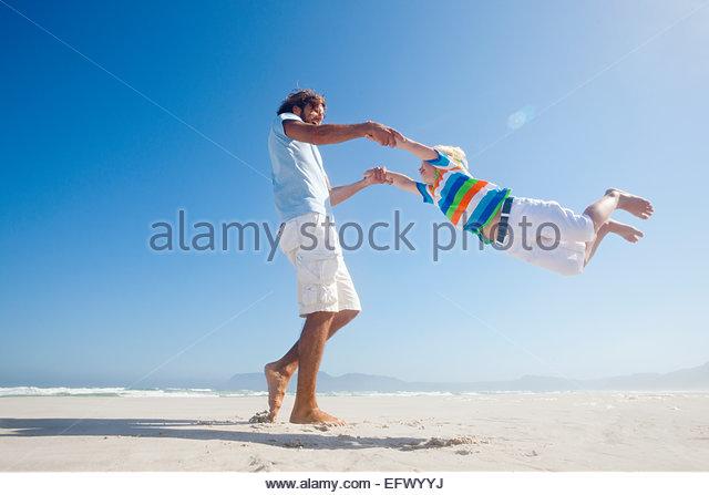 Lächelnd Vater schwingen Sohn um spielerisch am Sonnenstrand Stockbild