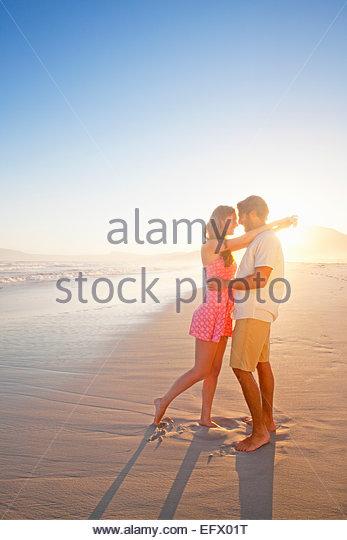 Romantisches Paar umarmen, in jeweils anderen Augen, am sonnigen Strand suchen Stockbild
