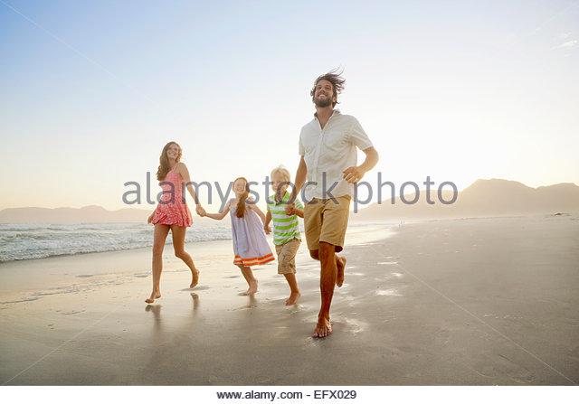 Glückliche Familie, Hand in Hand, läuft am Sonnenstrand Stockbild