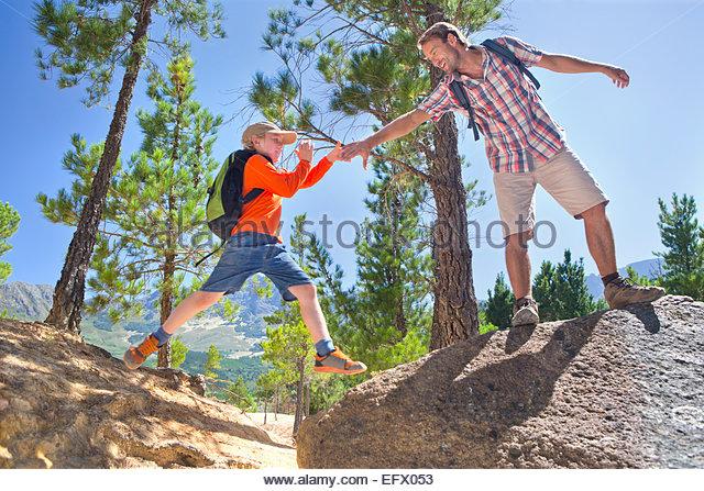 Vater Sohn helfen auf Bergpfad Klettern Stockbild