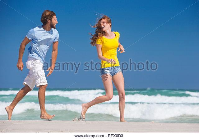Glückliches Paar, lachen, laufen am Sonnenstrand Stockbild