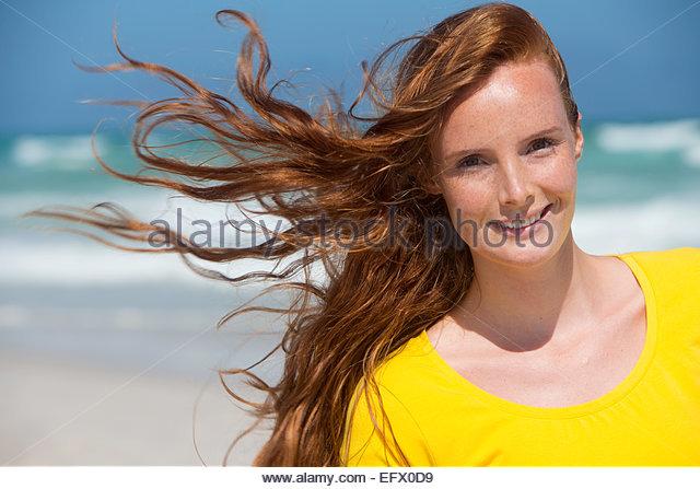 Porträt der lächelnde Frau mit roten Haaren am Sonnenstrand Stockbild