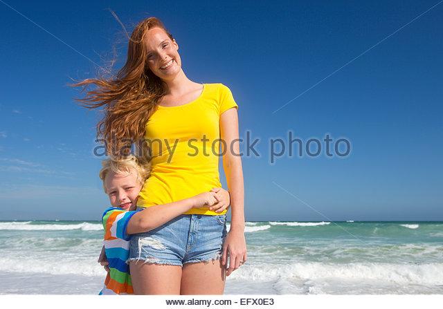 Porträt des Sohnes, mit Arme um lächelnde Mutter am Sonnenstrand Stockbild