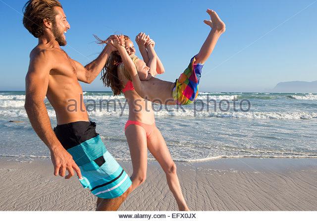 Glückliches Paar schwingenden Sohn in der Luft am Sonnenstrand Stockbild
