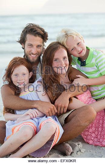 Porträt der Familie, lächelnd in die Kamera, umarmen am Sonnenstrand Stockbild