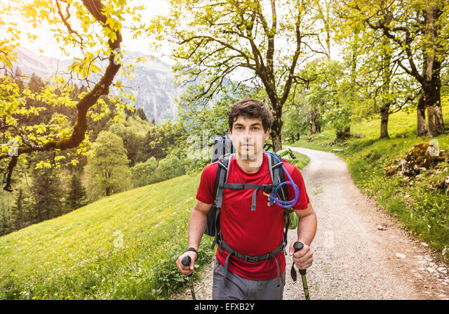 Junger Mann Wandern bis Landstraße, Oberstdorf, Bayern, Deutschland Stockbild