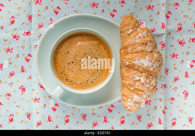 Schaumigen Kaffee in einem blauen Tasse und Untertasse auf einer floral Tischdecke mit Croissant Gebäck. Stockbild