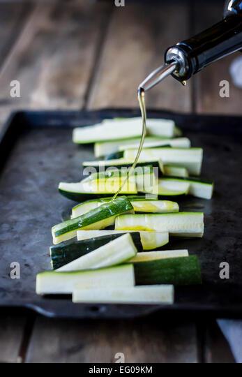 Zucchini auf ein Backblech mit Olivenöl Stockbild