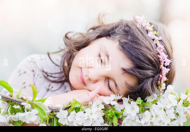 Niedliche Mädchen (4-5) schlafen auf Blumen Stockbild