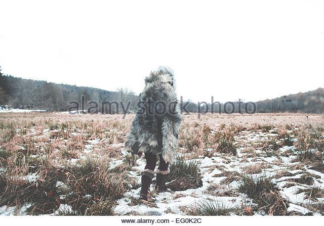 Frau trägt Pelz Mantel zu Fuß Weg über verschneite Wiesen Stockbild