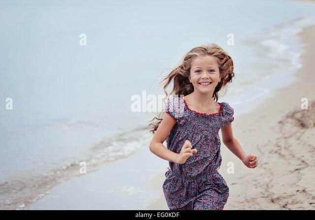 Schöne Mädchen (6-7) laufen am Strand Stockbild