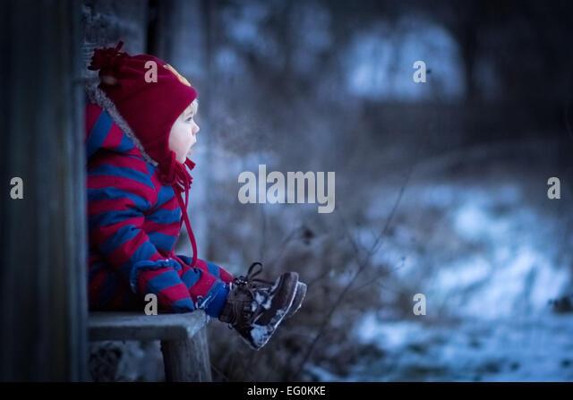 Kleiner Junge sitzt auf der Bank außerhalb Stockbild