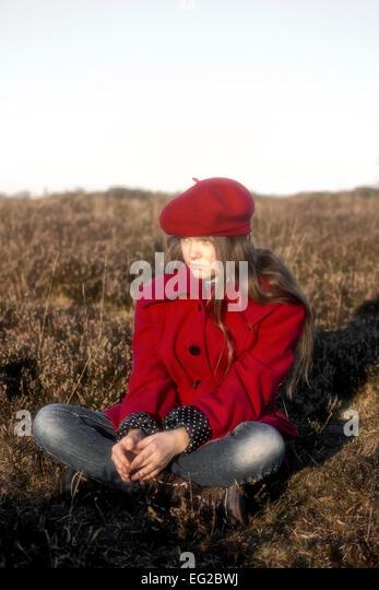 eine Mädchen in einem roten Mantel sitzt auf einem Hügel Stockbild