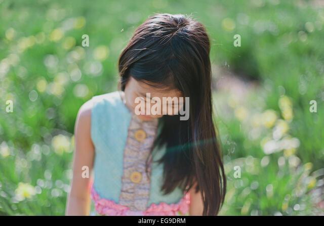 Mädchen (8-9) auf der Suche nach unten auf grüner Wiese Stockbild