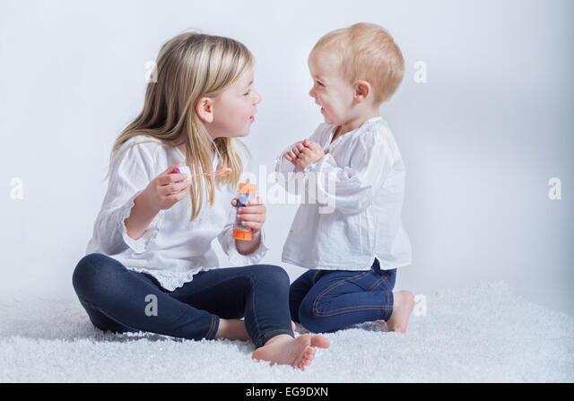 Geschwister (2-3, 6 und 7) spielen mit Blase wand Stockbild
