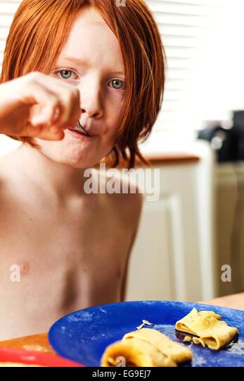 Junge beim Pfannkuchenfrühstück Stockbild