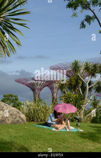 Singapur, Mutter und Tochter (2-3) unter Sonnenschirm im Garten entspannen Stockbild