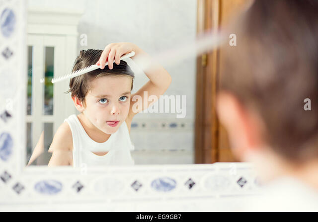 Junge stand vor einem Spiegel seine Haare kämmen Stockbild