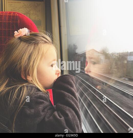 Mädchen auf der Suche durch Zugfenster Stockbild