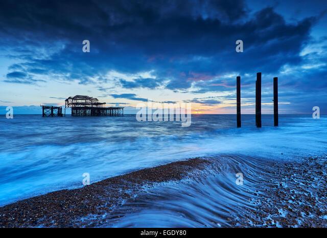 Die verwesenden Überreste der Brightons West Pier bei Sonnenuntergang mit den Gezeiten hereinkommen. Stockbild