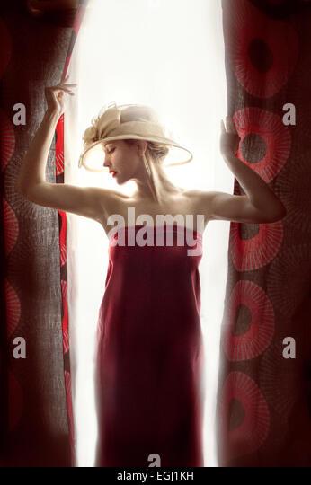 junge schöne Model posiert mit roten Vorhängen Stockbild